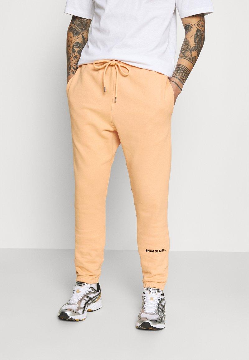 9N1M SENSE - LOGO PANTS UNISEX - Trousers - pantone apricot