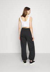 NA-KD - NA-KD X ZALANDO EXCLUSIVE - LOOSE FIT PANTS - Tracksuit bottoms - black - 2