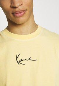 Karl Kani - SMALL SIGNATURE WASHED SLEEVELESS TEE - Triko spotiskem - light yellow - 5