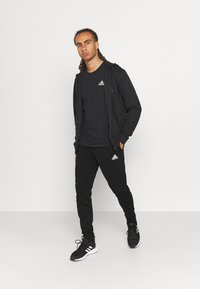 adidas Performance - Tracksuit bottoms - black - 1