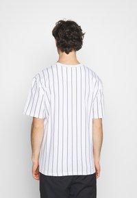 Karl Kani - SMALL SIGNATURE PINSTRIPE TEE UNISEX - Print T-shirt - white/black - 2