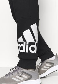 adidas Performance - ESSENTIALS - Tracksuit bottoms - black/white - 3