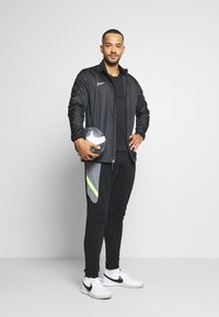 Nike Performance - DRY ACADEMY PANT  - Pantalon de survêtement - black/dark smoke grey/volt/light smoke grey - 1