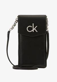 Calvin Klein - RE LOCK PHONE POUCH - Taška spříčným popruhem - black - 1