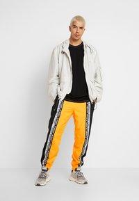 adidas Originals - REVEAL YOUR VOICE TRACKPANT - Tracksuit bottoms - flash orange - 1