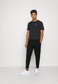 Nike Performance - Tracksuit bottoms - black - 1
