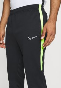 Nike Performance - ACADEMY PANT WINTERIZED - Tracksuit bottoms - black/volt