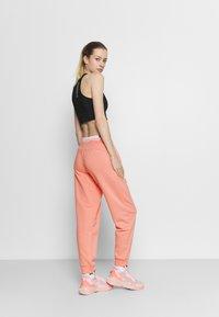 Puma - AMPLIFIED PANTS - Tracksuit bottoms - apricot blush - 2