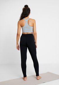 Curare Yogawear - PANTS LONG LOOSE ROLL DOWN - Tracksuit bottoms - black - 2