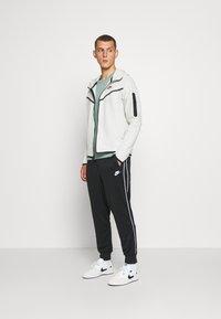 Nike Sportswear - REPEAT - Teplákové kalhoty - black - 1