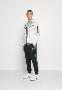 Nike Sportswear - REPEAT - Tracksuit bottoms - black - 1