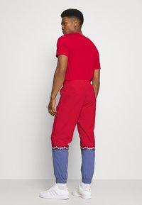 adidas Originals - SLICE TREFOIL ADICOLOR PRIMEGREEN ORIGINALS SLIM TRACK - Pantalones deportivos - scarlet/crew blue - 2