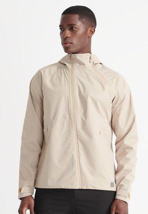 SPORT TRAINING ASYMMETRIC - Waterproof jacket - malt