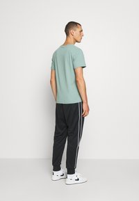 Nike Sportswear - REPEAT - Tracksuit bottoms - black - 2