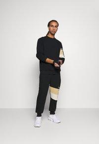 Hummel - HMLAIDAN REGULAR PANTS - Tracksuit bottoms - black - 1