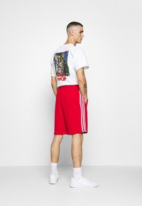adidas Originals - 3-STRIPE UNISEX - Tracksuit bottoms - red - 2