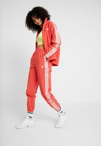 adidas Originals - LOCK UP ADICOLOR NYLON TRACK PANTS - Tracksuit bottoms - trace scarlet/white - 1