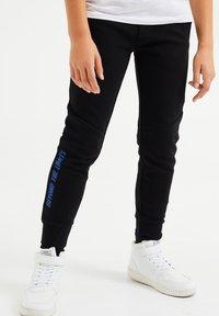 WE Fashion - Tracksuit bottoms - black - 1
