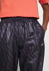 Nike Sportswear - Tracksuit bottoms - dark raisin/bright mango - 4