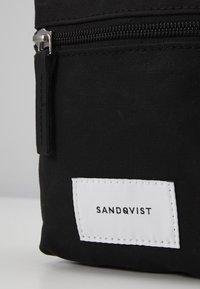 Sandqvist - SIXTEN - Taška spříčným popruhem - black - 2