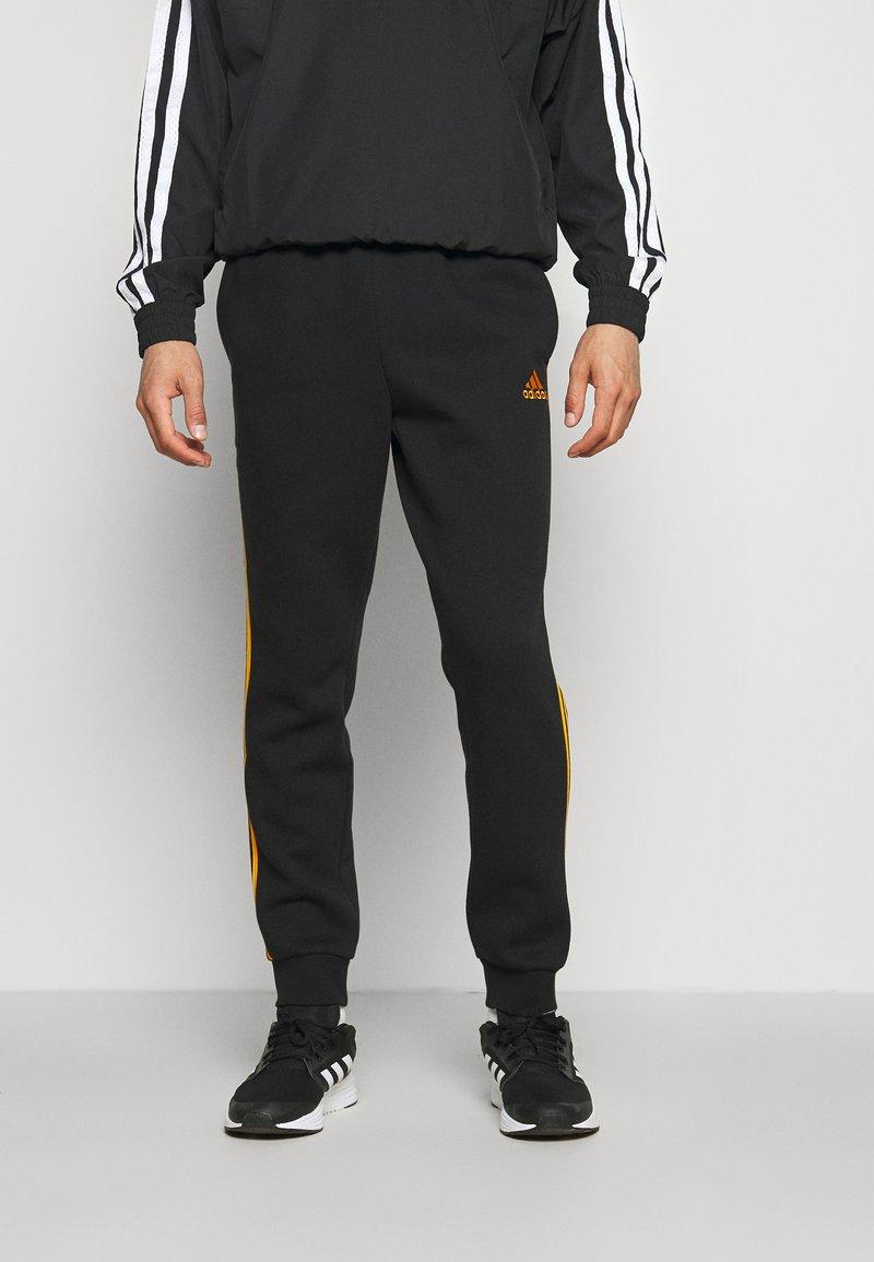 adidas Performance - 3 STRIPES  ESSENTIALS - Tracksuit bottoms - black/semi solar gold