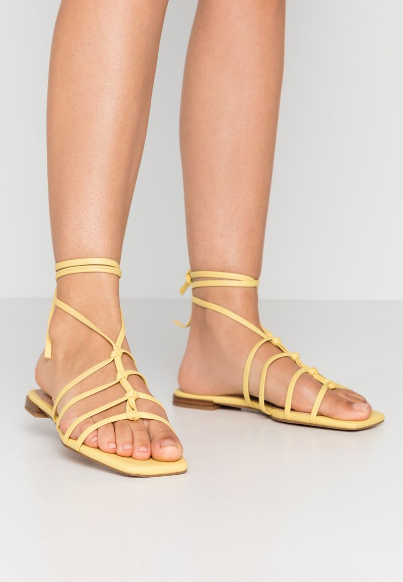NA-KD - CROSSED STRAPS FLATS - Sandály - light yellow