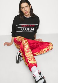 Versace Jeans Couture - PRINT BAROQUE - Tracksuit bottoms - red - 4