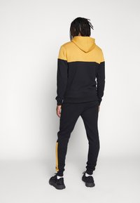 CLOSURE London - CONTRAST SCRIPT JOGGER - Tracksuit bottoms - black/mustard - 2