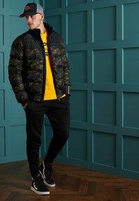 Superdry - TRACK SPORT PUFFER - Winter jacket - camo/black - 1