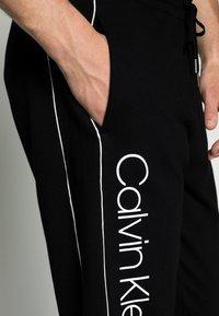 Calvin Klein - LOGO PRINT - Spodnie treningowe - perfect black - 4