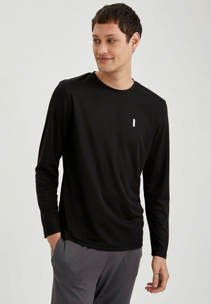 DeFacto Camiseta de manga larga con bolsillo para mujer.