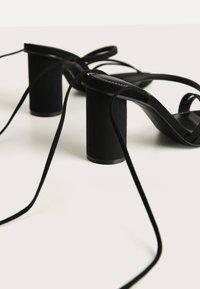 Bershka - MIT BREITEM ABSATZ UND SCHNÜRRIEMCHEN  - Korolliset sandaalit - black - 6