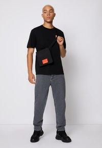 Calvin Klein Jeans - RELAXED BADGE TEE UNISEX - Print T-shirt - black - 3