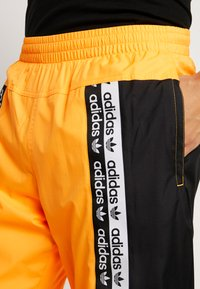 adidas Originals - REVEAL YOUR VOICE TRACKPANT - Tracksuit bottoms - flash orange - 3