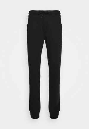 DISCUS - Tracksuit bottoms - black