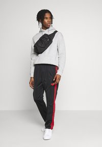 adidas Originals - SUPERSTAR 3STRIPES TRACK PANTS - Tracksuit bottoms - black/red - 1