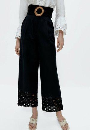 MIT SCHNALLE - Trousers - black