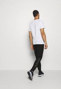 Puma - AMPLIFIED PANTS - Pantalon de survêtement - black - 2