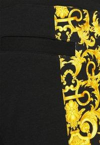 Versace Jeans Couture - PRINT LOGO BAROQUE - Tracksuit bottoms - black - 7