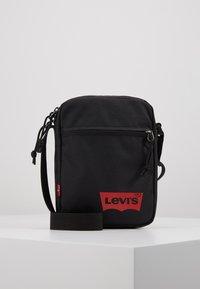 Levi's® - MINI CROSSBODY SOLID BATWING - Taška spříčným popruhem - regular black - 0