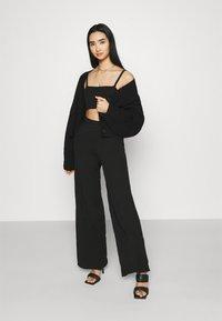 NA-KD - NA-KD X ZALANDO EXCLUSIVE SOFT RIBBED PANTS - Trousers - black - 1