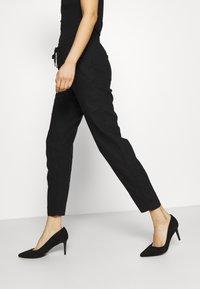 Marks & Spencer London - TAPERED - Trousers - black - 3