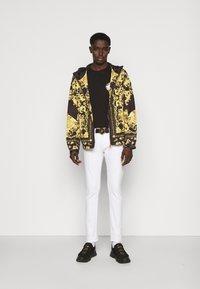 Versace Jeans Couture - T-shirt z nadrukiem - black / gold - 1