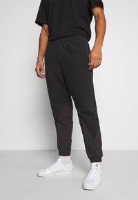 adidas Originals - UNISEX - Tracksuit bottoms - black - 0