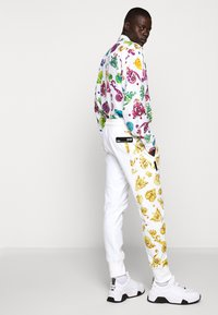 Versace Jeans Couture - JOGGERS GIOIELLI SIDE STRIPE - Tracksuit bottoms - white - 4