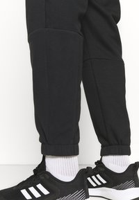 adidas Performance - ESSENTIALS RELAXED - Tracksuit bottoms - black - 4