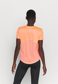 Nike Performance - MILER - T-shirt med print - bright mango/silver - 2