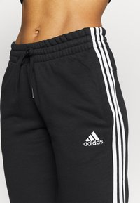 adidas Performance - ESSENTIALS FRENCH TERRY STRIPES PANTS - Verryttelyhousut - black/white