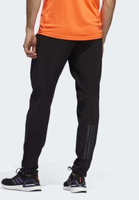 adidas Performance - OWN THE RUN ASTRO JOGGERS - Tracksuit bottoms - black - 1