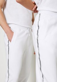 HUGO - DOAK METALLIC UNISEX - Tracksuit bottoms - white/silver - 4